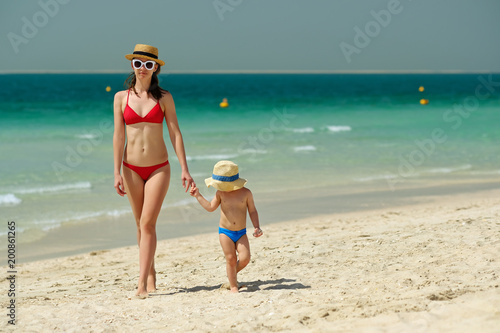 Toddler boy walking on beach with mother