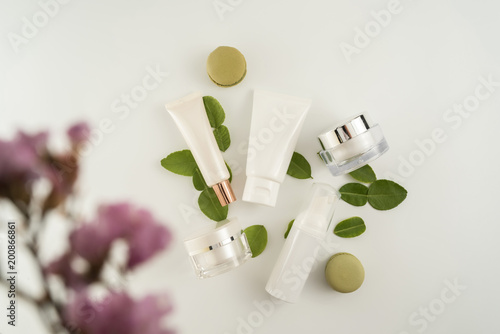 White cosmetic products and green leaves on white background. Natural beauty blank label for branding mockup concept.
