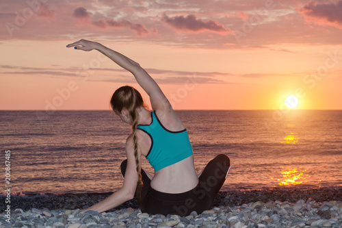Foto op Aluminium School de yoga Girl practicing yoga on the beach. View from the back, sunset