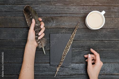 Piórko w kobiecej dłoni, zeszycie i filiżankę kawy. Stary drewniany stół. Widok z góry