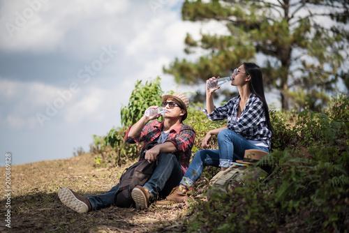 Młody wycieczkowicz odpoczywać i woda pitna w lesie