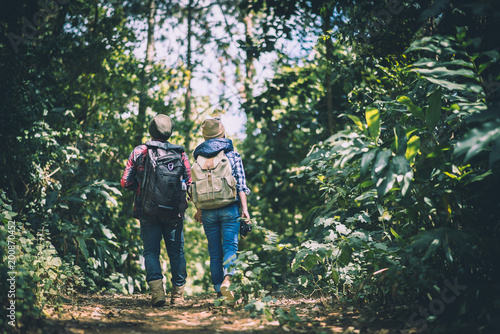 Young couple walking with backpacks in forest. Adventure hikes, Enjoy holidays together,