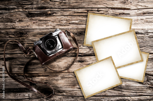 Retro camera and blank photo frames on wooden table. Top view.
