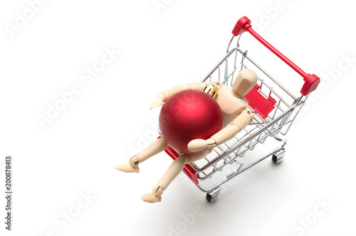 Wooden doll and christmas ball and shopping cart on white background : economy concept