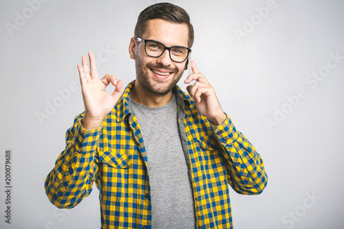 Smiling young casual man talking on the phone and making ok sign on the grey background.