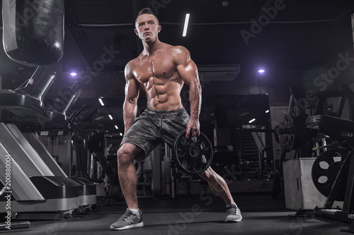 Poster Handsome man doing exercises in the gym on a dark background, using dumbbells, doing sports exercises for the development of the muscles of the back, biceps, triceps.
