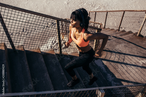 Keuken foto achterwand Jogging Woman running up the stairway along the beach
