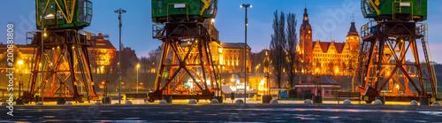 Obraz na płótnie Historical harbor cranes on riverside boulevards in the evening, after a spring downpour