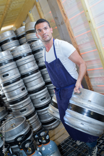 worker carrying barrels of beer at the brewery