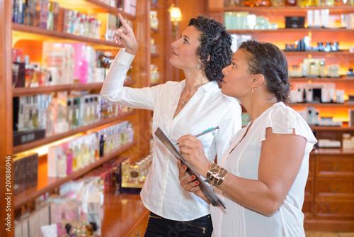Plexiglas Apotheek Lady pointing to product on shelf, woman noting on clipboard