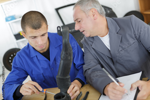 student with teacher during automotive class
