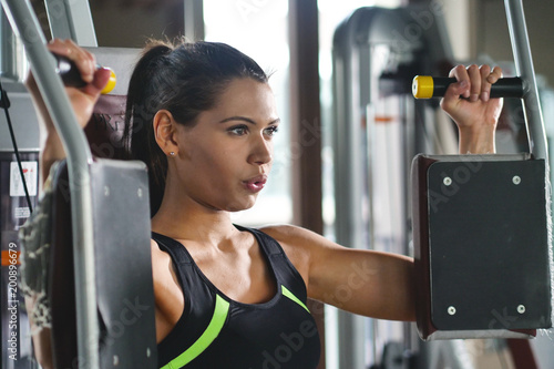 Poster Beautigul fit woman (girl) trains in the gym. Concept: Sport, passion, fitness, love.