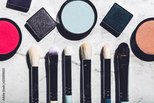 Foto Murales Makeup brushes and eyeshadows on a marble background