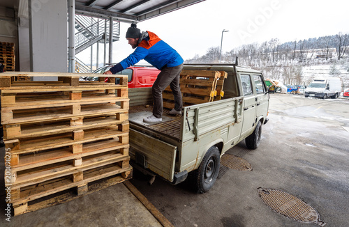Man is loading wooden pallets on a truck in winter. Stacking wooden euro pallets on a truck lorry container for shipping and transport.