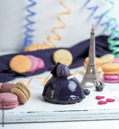 lilac round cake with macarons on a white wooden board,