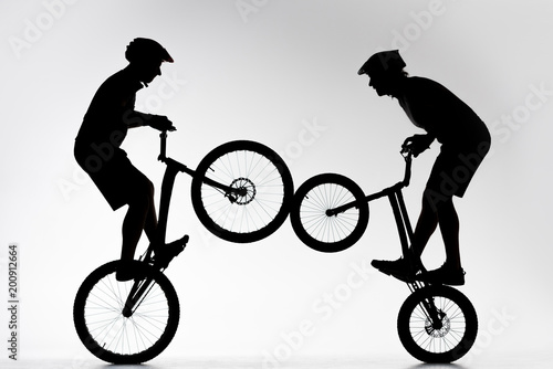 silhouettes of trial bikers performing stunt synchronously on white