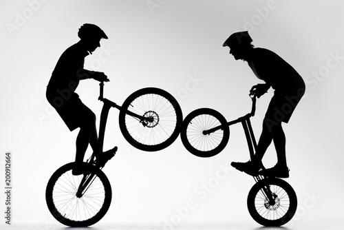 sylwetki rowerzystów próbnych wykonujących kaskadowo synchronicznie na białym tle