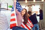 Girl with a beautiful smile with the flag of america indoors. Independence Day of the USA. - 200913433