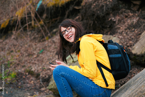 A girl in glasses travels near a mountain stream with a telephone.