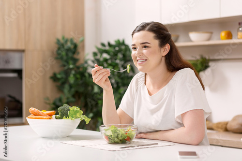 canvas print picture Favorite food. Joyful gay woman smiling and eating salad