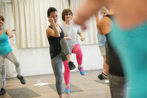 Group of senior people in fitness room exercising with coach - 200919275