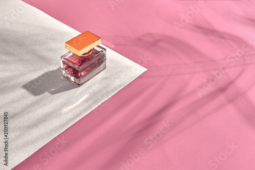 Fashionable Women's Cosmetics and Accessories. Flat Lay. Perfume. Pink and white background. Shadow from a palm leaf - 200927845