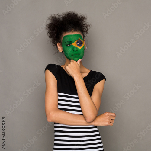 Foto Murales Young woman with Brasil flag painted on her face