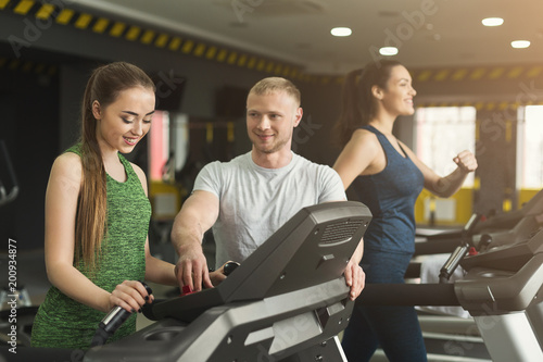 Poster Fitness coach helps woman on elliptical trainer
