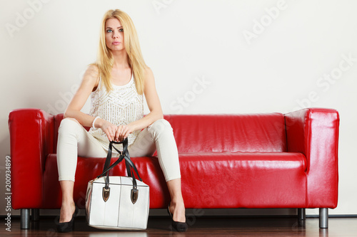 Woman sitting on sofa holding white bag