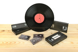 Composition of vinyl disc, audiocassettes and videocassettes on wooden table.