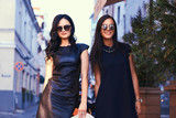 Two sexy brunette wearing stylish black dresses in sunglasses, posing near a terrace cafe in a city. - 200937276