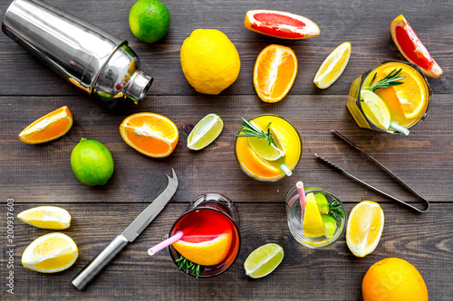 Foto Murales Mix exotic fruit cocktail with alcohol. Shaker and strainer near citrus fruits and glass with cocktail on dark wooden background top view pattern