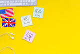 Study english online.English for kids. Elementary. British and american flags, computer keyboard, stickers with vocabulary on yellow background top view copy space