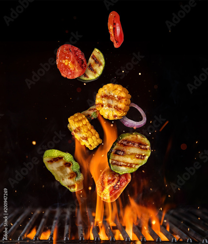 Foto Murales Flying pieces of vegetable from grill grid, isolated on black background