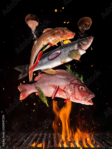 Flying raw whole fish from grill grid, isolated on black background