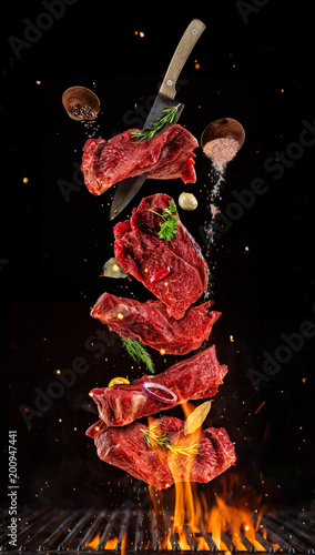 Flying pieces of raw beef steaks from grill grid on black background.
