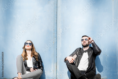 Foto Murales Couple sitting on the blue wall background