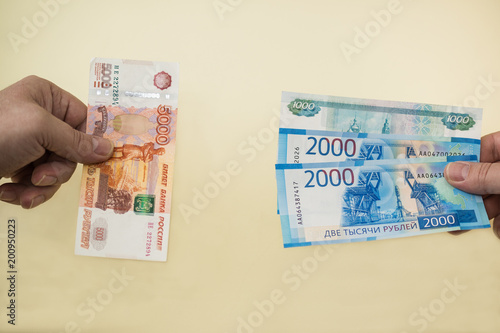 Equivalent exchange of one five thousand Russian banknotes for smaller money in two and one thousand rubles. New money