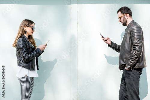 Couple with phones on the green background