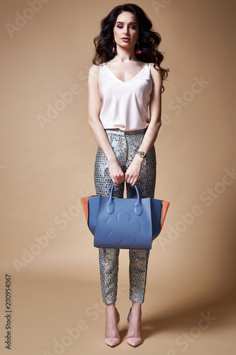 Sexy beautiful woman fashion glamour model brunette hair makeup wear silk blouse trousers clothes for every day casual party style accessory bag jewelry date walk girlfriend skinny body shape studio.