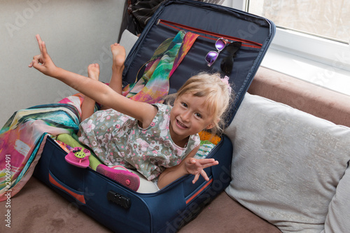 A small tanned cute little girl traveler gathers a suitcase. She indulges and helps her mother to pack things carefully. Tourist attribute. Order in suitcase. Cild. Kid.