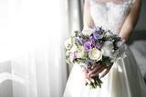 Brides wedding bouquet with peonies, freesia and other flowers in women's hands. Light and lilac spring color. Morning in room - 200963641
