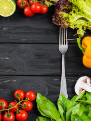 Culinary black wooden frame background with fresh vegetables, yellow paprika pepper, basil, cherry tomatoes, mushrooms, red onion, lime, lettuce. Food top view. Fork in the middle.