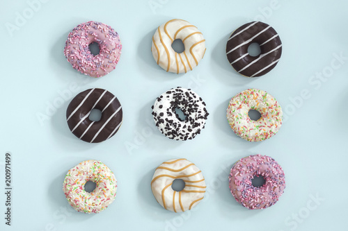 Foto Murales Sweet and colourful donuts glazed with sprinkles. Set of different type of donuts on the blue background.