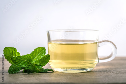 Close up a glass cup of mint tea with green fresh peppermint leaves , relaxation and healthy drink
