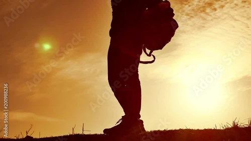 Man student reading in the park with backpack against sunset. Silhouette of man reading book at sky sunset nature lifestyle warm tone