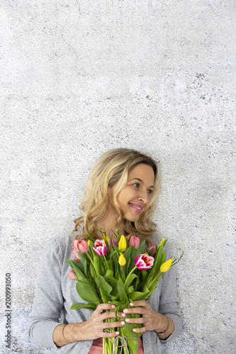 Foto Murales Young pretty woman with a bouquet of flowers stands in front of concrete wall and is happy about mother's day, birthday, wedding day