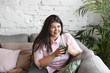 Horizontal shot of charming obese young female choosing healthy lifestyle drinking green spinach smoothie in modern living room, smiling happily, enjoying fresh taste. Weight loss and detoxication
