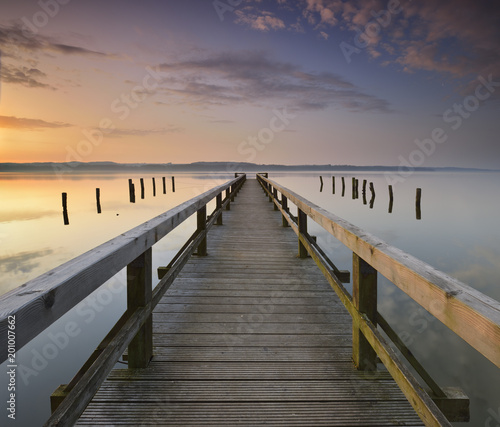 Plexiglas Pier Calm Lake at Sunrise, Long Wooden Pier
