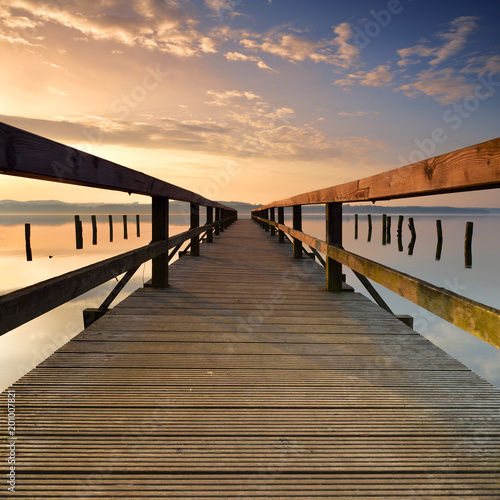 Acrylglas Pier Lake with Long Wooden Pier at Sunrise